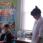 Child with experiment being watched by female in white lab coat.